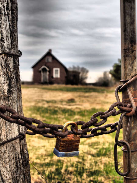 Lock and chain with barn in background with dramatic sky